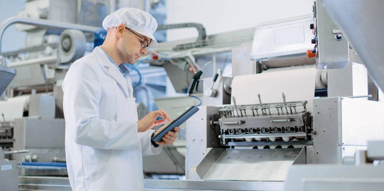 Técnico trabalhando com tablet em fábrica automatizada. Quais as características de um lubrificante de grau alimentício?   NSF international